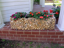 Rock container with flowers Stock Photo