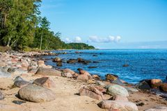 Rock covered beach in countryside in Latvia, large rocks in water. With calm wind and sunshine royalty free stock photography