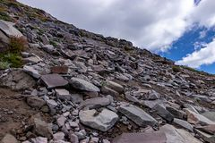 rock covered hillside with blue skys through clouds royalty free stock photo