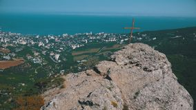 Landscape view on Rock with a Cross in the Mountains. Rock with a cross in the mountains. Landscape view from above on a small town and the sea. Mount Stavrikai stock footage