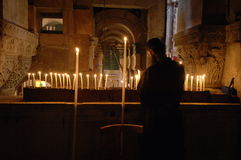 Rock of Crucifixion. September 16, 2006 - A Coptic monk tends to candles left in prayer atop the site of Christ's crucifixion, now in the Church of the Holy Stock Photography