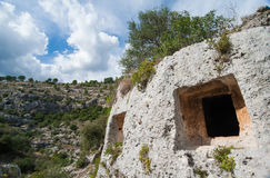 Rock cut tomb. In the necropolis of Pantalica, East Sicily and cloudy sky royalty free stock photo