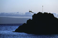 Rock Diver. Human form diving off rocky outcropping.  Figure is silhouetted against blue dusky sky.  Location: Black Rock, Kaanapali Beach, Maui, Hawaii Royalty Free Stock Photo