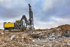 Rock drilling machine to make hole and build a building stock image