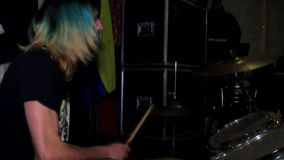 Rock drummer man with colorful hair and beard. A young male drummer at a music rehearsal. he has colored yellow-blue hair and a black beard. Flag of Ukraine in stock video footage