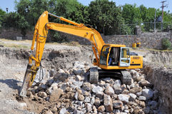 Rock excavator. Pic of an excavator working on rocks Stock Photos