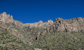 Rock face and saguaro cacti against a blue sky in Sabino Canyon,. Rock cliffs and saguaro-studded hillside against a deep blue sky in Sabino Canyon, Tucson Royalty Free Stock Photography