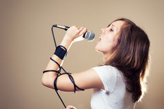 Rock female vocalist on gray background royalty free stock photos