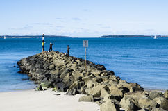 The Calm blue ocean waters with a man fishing on rocky coast of Dolls Point Beach, Brighton Le Sands, Sydney, Australia. A Calm blue ocean waters with a man royalty free stock images