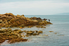 Man fishing from rocks in ocean  Royalty Free Stock Photography