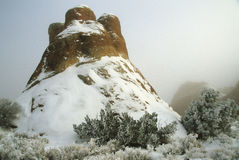 Rock in fog. A hillock shaped rock swathed in snow and fog. At Arches National Park Utah Stock Photography