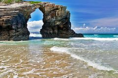 The rock in the form of an arch on the ocean beach. Northern Spain, Praia de Augas Santas, sunny summer day Stock Image