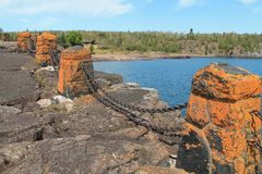 Rock Formation Along Lake Superior. Rock formation along the shore of Lake Superior with orange pillars and a forest skyline in the back along with blue water Stock Image