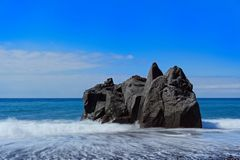 Rock formation on the beach against clear blue sky. Praia Formosa beach in Funchal on Portuguese island of Madeira royalty free stock image