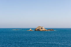 Rock formation in blue sea. Scenic view of rock formation protruding from blue ocean Stock Photo