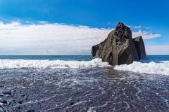Rock formation and the flowing water against blue sky. Praia Formosa beach, Funchal, Portuguese island of Madeira royalty free stock photos