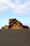 Rock formation on island Lanzarote. Rock on beach on island of Lanzarote with sky Stock Images