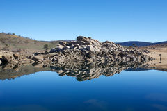 Rock Formation Lake Reflection. Unusual rock formation makes perfect landscape reflection on lake in dry country field Stock Photo