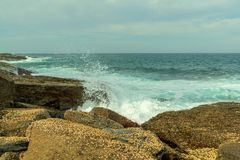 Waves breaking on Rock Formation, and rock pool on the Coastline at Pebbly Beach NSW royalty free stock image
