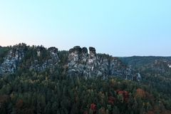 Rock formation with trees in the autumn of Elbe sandstone mountain in the evening stock photo