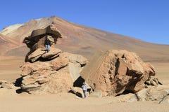 Rock formation in Uyuni, Bolivia known as Arbol de Piedra. Salar de Uyuni  Bolivia - April 11 2014 - Tourists climbing on the rock formation in Salar de Uyuni Royalty Free Stock Photos