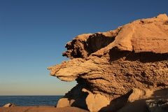 Rock formations on the beach at sunset Stock Photography