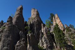 Rock Formations in Custer State Park. Eroded rock formations and trees stand tall against a clear blue spring sky in Custer State Park, South Dakota stock photography