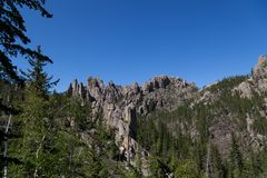 Rock Formations in Custer State Park. A mountain eroded to expose spires of tall quartz rock among a forest in Custer State Park, South Dakota royalty free stock image