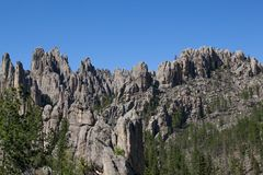 Rock Formations in Custer State Park. A mountain eroded to expose spires of tall quartz rock among a forest in Custer State Park, South Dakota stock photo