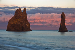 Rock formations and dramatic clouds on black beach at sunset Stock Image