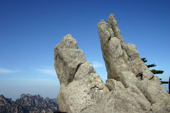 Rock formations on mountain. Scenic view of unusual rock formations on mountainside with blue sky background Royalty Free Stock Photo