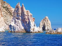 The rock formations of Polyaigos, an island of the Greek Cyclades. Fantastic cliffs and rock formations rise from the crystal blue sea on Polyaigos near the royalty free stock photo