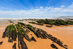 Rock formations on sandy beach Portugal. Royalty Free Stock Photography