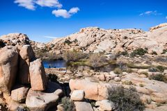 Rock formations surrounding Barker Dam, tourists relaxing on the shoreline; Joshua Tree National Park, California royalty free stock photography