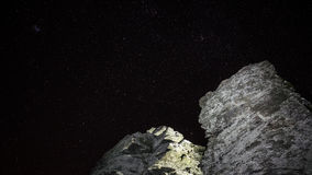 Rock in front of night sky. Illuminated rocks in front of sky full of stars Stock Photos