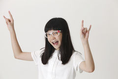 Rock gesture. Happy girl standing raising her arm with rock sign Royalty Free Stock Images