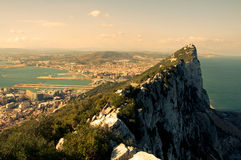 Rock of Gibraltar. Steep rocky coastal lookout point ridge and cliffs overlooking ocean with a city in the distance Stock Photos