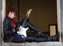 Rock girl. Sitting on the window of an empty house playing electric guitar Royalty Free Stock Images