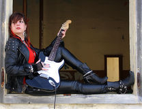 Rock girl. Playing the electric guitar sitting on a window of a abandoned house Stock Photos