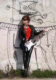 Rock girl. Plays the electric guitar beside a graffiti wall of an abandoned house Royalty Free Stock Photography