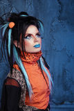 Rock girl with blue lips and punk hairstyle leaning against grun. Ge wall Stock Image