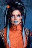 Rock girl with blue lips and punk hairstyle leaning against grun. Ge wall Stock Photos