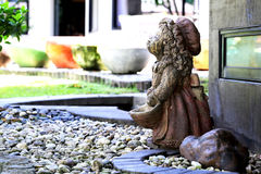 Rock girl doll in the pebble garden Royalty Free Stock Image
