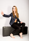Rock girl in a leather jacket leather shorts. girl sitting on the case Stock Photos