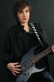 Rock girl in leather outfit with electric guitar Stock Photo