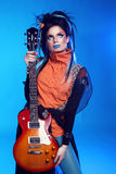 Rock girl posing with electric guitar  on blue backgroun Stock Images