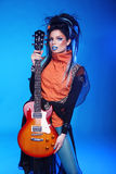 Rock girl posing with electric guitar  on blue backgroun Stock Photo