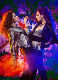 Rock girls. Fashion portrait of two glam rock girls posing on colorful background;  slightly inversed Stock Photography