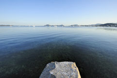 Rock and glassy water Royalty Free Stock Image