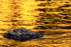 Rock and gold autumn lake reflections Royalty Free Stock Photography